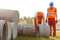 Construction worker rolling concrete pipe Royalty Free Stock Image