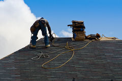 Construction worker on the roof. Construction worker installing shingles on the roof Stock Photo