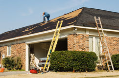 Construction Worker. Roofer repairing the roof of a brick house in the suburbs Royalty Free Stock Image