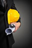 Construction worker's hand holding project documents and helmet Royalty Free Stock Photography