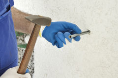 Construction worker`s hands in the protective gloves attach the anchor bolt to the wall of the building. Stock Photo