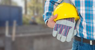 Construction Worker with safety gloves and hat in front of construction site. Digital composite of Construction Worker with safety gloves and hat in front of Royalty Free Stock Photo