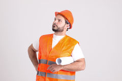 Construction Worker in Safety Helmet with Building Plans. Handsome Construction Worker in Safety Helmet and Orange Reflex Jerkin is Holding a Building Plans Royalty Free Stock Images