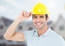 Construction Worker with safety helmet in front of construction site. Digital composite of Construction Worker with safety helmet in front of construction site Royalty Free Stock Images