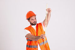 Construction Worker in Safety Helmet is Measuring with Meter. Young Construction Worker in Safety Helmet and Orange Reflex Jerkin is Measuring with Measuring Royalty Free Stock Photos