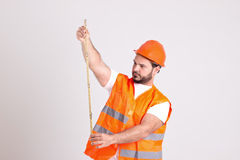Construction Worker in Safety Helmet is Working with Measuring T. Handsome Construction Worker in Safety Helmet and Orange Reflex Jerkin Isolated on White Stock Photos
