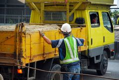 Construction worker and sand t. Worker directing a sand-filled dump truck at a construction site Stock Photo