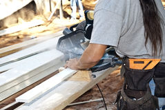 Construction Worker/Sawing. A construction worker at a new home cutting the hardiplank royalty free stock image