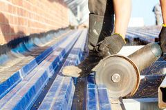 Construction worker sawing steel sheet Royalty Free Stock Images