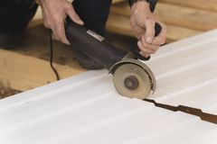 Construction worker sawing steel sheet with trapezoidal profile royalty free stock image