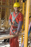 Construction Worker Saws Board Smiling - Vertical Royalty Free Stock Photo