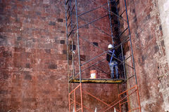 Construction worker on scaffolding working on textured wall Stock Photography