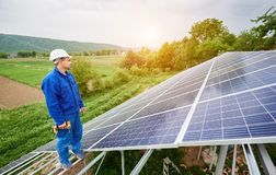 Installing of solar photo voltaic panel system. Construction worker with screwdriver standing on metal frame of photo voltaic solar system looking on shiny stock photo