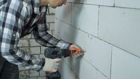 Construction worker screwing in screws into block wall with electric drill. Construction worker screwing in screws into aerated concrete block wall with electric stock video