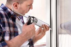 Construction worker sealing window with caulk. Indoors stock images