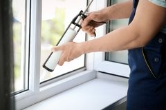 Construction worker sealing window with caulk indoors. Construction male worker sealing window with caulk indoors royalty free stock photography