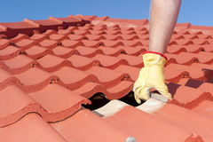 Construction worker shingle roofing repair. Roof repair, worker with yellow gloves replacing red tiles or shingles on house with blue sky as background and copy Royalty Free Stock Images