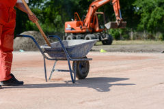 Construction worker with shovel and blue mortar cart Stock Images