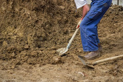 Construction worker shoveling dirt Stock Photo