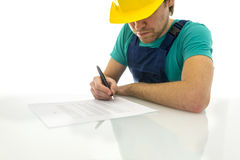 Construction worker signing contract. Young construction worker signing contract on white desk. Over white background Stock Image