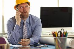 Construction Worker Sit in Engineering Office. Bored Caucasian Architect Builder Wearing Shirt and Yellow Hard Hat with Mobile Phone in Hand, Appoint Meeting stock photography