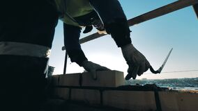 Construction worker at a construction site. Bricklaying is being carried out by a male constructor