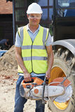 Construction Worker On Site Holding Circular Saw Royalty Free Stock Image
