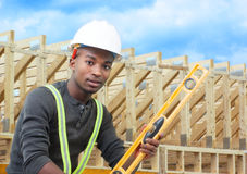 Construction worker on site holding level with white helmet. Construction site worker with level helmet and beams background Stock Images