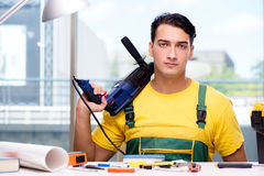 The construction worker sitting at the desk Stock Image