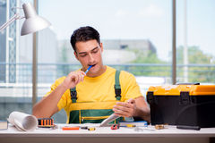 The construction worker sitting at the desk Royalty Free Stock Photo