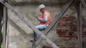 Construction worker sitting on wooden scaffolding and using tablet PC. In summer day stock footage