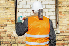Construction worker with a sledgehammer at brick wall Royalty Free Stock Photo