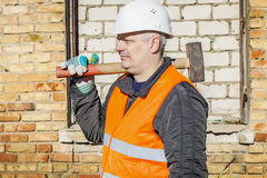 Construction worker with sledgehammer near the brick wall Stock Images