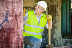 Construction worker with sledgehammer near wall Stock Photography