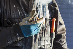 Construction worker smokes a cigarette in Finland. He is wearing dirty overalls and working gloves in his hand. The sun is shining strongly on the side Stock Image