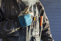 Construction worker smokes a cigarette in Finland. He is wearing dirty overalls and working gloves in his hand. The sun is shining strongly on the side Royalty Free Stock Photography