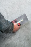 Construction worker smoothing - plastering concrete wall by a st Royalty Free Stock Photography