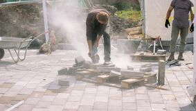 The construction worker use electric concrete cutter cut a stone Royalty Free Stock Photos