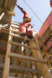 Construction Worker Stands on Ladder - Vertical Royalty Free Stock Photography
