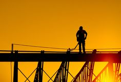 Construction worker. Stands on steel beam of building at sunrise Royalty Free Stock Image