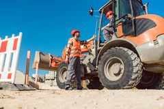 Construction worker starting road works on site. With machine stock photo