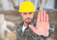 Construction Worker with stop hand gesture in front of construction site. Digital composite of Construction Worker with stop hand gesture in front of Royalty Free Stock Image