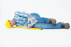 Construction worker suffering from knee pain. Full length of construction worker suffering from knee pain while lying against white background Royalty Free Stock Photos