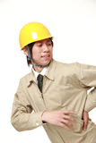 Construction worker suffers from lumbago. Studio shot of young Japanese man on white background Royalty Free Stock Photography