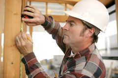Construction Worker Takes Measurments. A construction working taking measurments and marking a wood beam on a house frame Stock Image