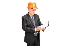 Construction worker taking notes on a clipboard. Mature construction worker taking notes on a clipboard isolated on white background Stock Image
