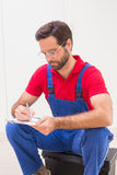 Construction worker taking notes on clipboard. In a new house Royalty Free Stock Photo
