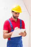 Construction worker taking notes on clipboard. In a new house Stock Images