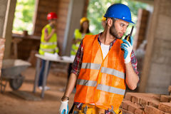 Construction worker talking on walkie talkie at site. Young construction worker talking on walkie talkie at building site stock photo