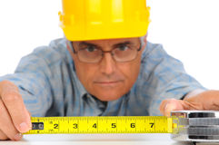 Construction Worker with Tape Measure. Closeup of a construction worker in hard hat using a measuring tape with the numbers facing forward. Focus is on the mans Royalty Free Stock Photos